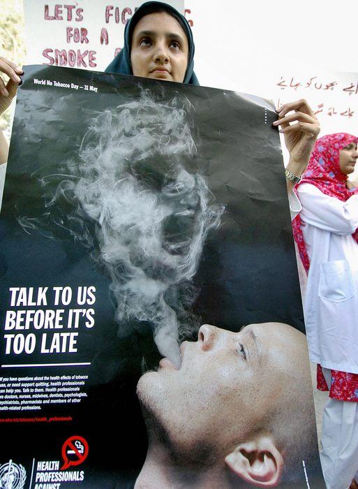 Пакистанская женщина-врач держит плакат против курения во время демонстрации в Карачи 30 мая 2005 года. 31 мая отмечается международный день некурящих. Фото: AAMIR QURESHI/AFP/Getty Images
