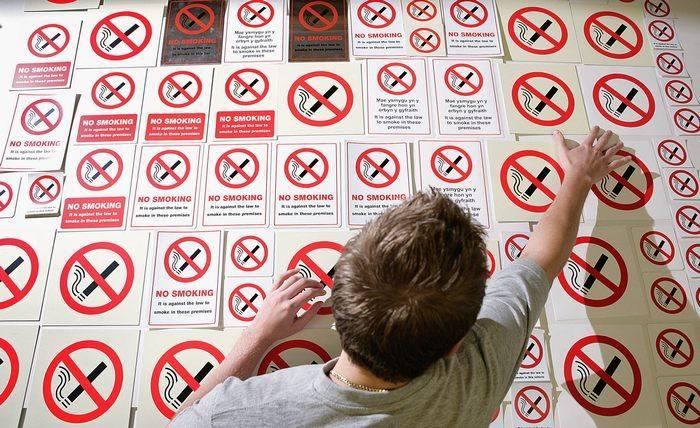 Работник фабрики показывает знаки о запрете курения 22 мая 2007 года в городе Кеттеринг, Англия. Курение в закрытых общественных помещениях запрещено в Англии с 1 июля 2007 года. Фото: Peter Macdiarmid/Getty Images