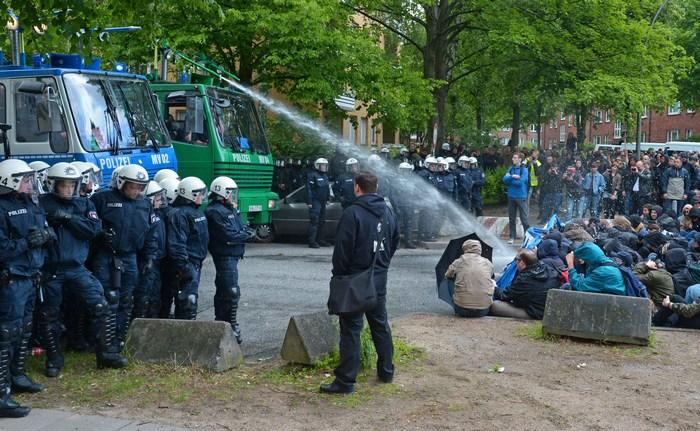 Когда в середине дня прибыли неонацисты, их противники, сидя, заблокировали запланированную для марша дорогу по улице Эльбекервег. Полицейским пришлось уносить их с дороги и поливать из водомётов. Фото: Фото: Thomas Starke/Getty Images
