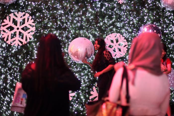 Люди фотографируются у большой украшенной ёлки на Орчард Роад. Фото: Chris McGrath / Getty Images