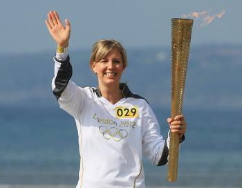 Джоанна Дикенсон (Johanna Dickinson) несёт факел эстафеты олимпийского огня. Фото: Matt Cardy/Getty Images