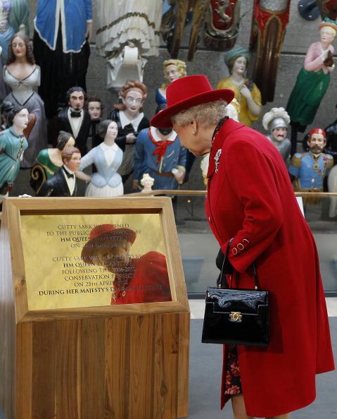 Елизавета II читает надпись на доске, сделанную в честь официального открытия  «Катти Сарк». Фоторепортаж. Фото: Jamie Wiseman/WPA Pool/Getty Images