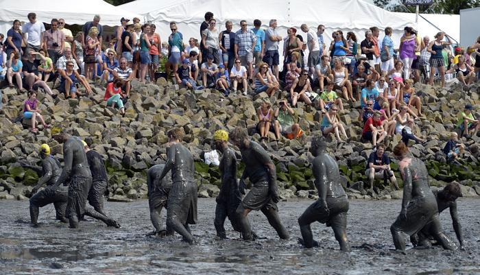 Благотворительная Грязевая Олимпиада (Wattoluempiade) состоялась на побережье Северного моря в немецком городе Брунсбюттелле 28 июля 2013 года. Фото: Patrick Lux/Getty Images