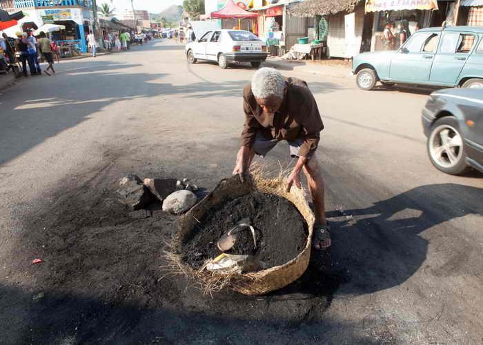Человек собирает пепел и кости в селе Амбатолоака на Нуси-Бе. Где были убиты и сожжены трое мужчин разъярённой толпой жителей, подозреваемых в убийстве восьмилетнего мальчика для изъятия его органов. Фото: RIJASOLO/AFP/Getty Images