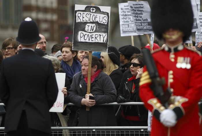 Протестующие держали плакаты на улицах во время торжественных похорон британского экс-премьера Маргарет Тэтчер. Фото: JUSTIN TALLIS/AFP/Getty Images