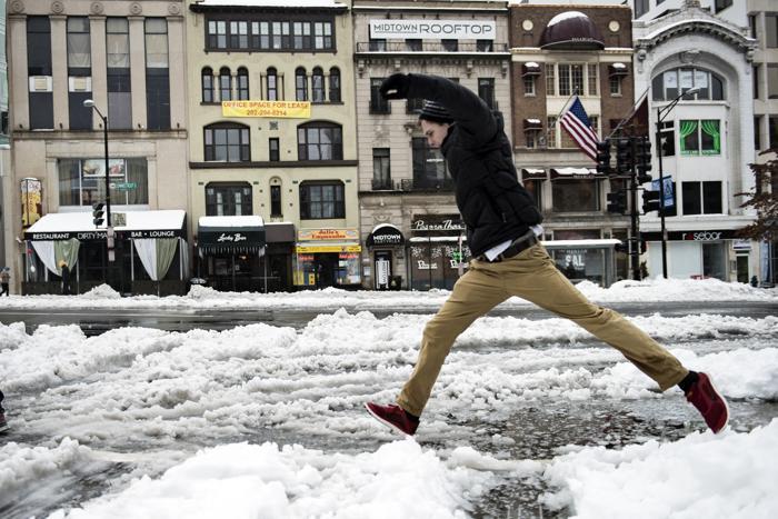 Человек прыгает через лужу на Коннектикут-авеню в Вашингтоне 13 февраля 2014 года. Фото: BRENDAN SMIALOWSKI/AFP/Getty Images