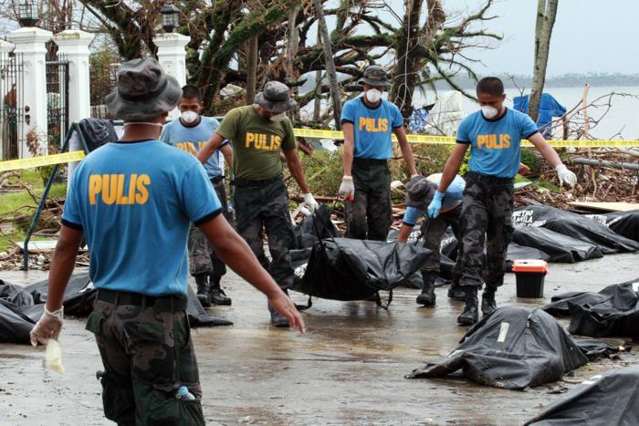 Члены Филиппинской национальной полиции несут сумки с телами жертв супертайфуна «Хайян». Фото: Jeoffrey Maitem / Getty Images