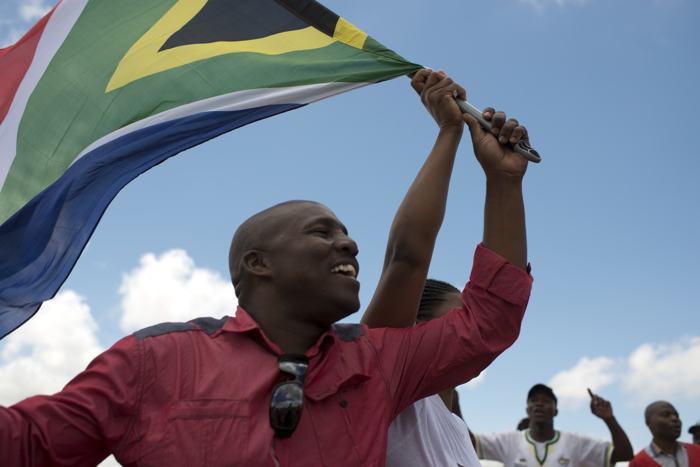 Люди танцуют и поют с национальным флагом во время похорон Нельсона Манделы в деревне Куну 15 декабря 2013 года. Фото: PEDRO UGARTE/AFP/Getty Images