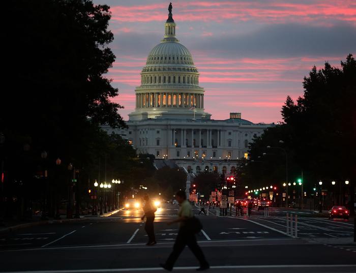 Солнце начинает подниматься за зданием Капитолия США на следующее утро после принятия законопроекта о возобновлении работы правительства 17 октября 2013 года. Фото: Mark Wilson / Getty Images