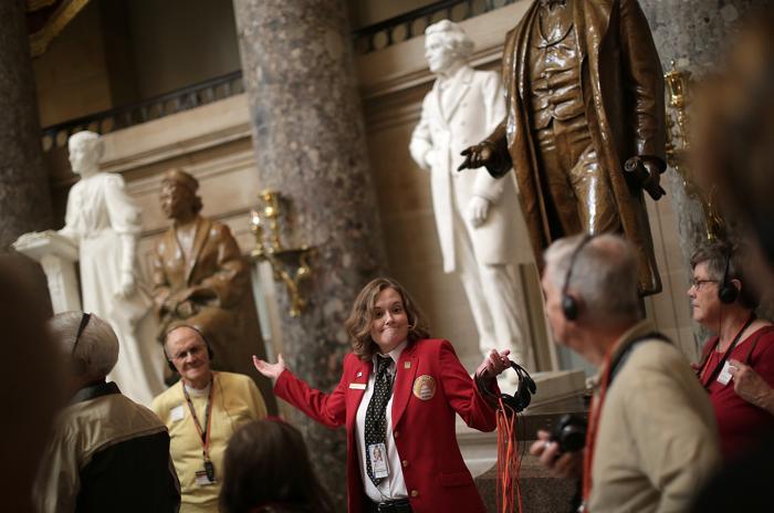Экскурсовод Кэтрин Минахан в Капитолии США проводит экскурсию в Скульптурном зале после выхода на работу, когда был принят закон о возобновлении работы правительства США. Фото: Win McNamee / Getty Images