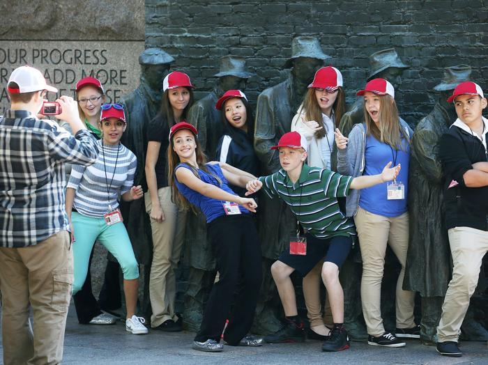 Восьмиклассники средней школы в Парме, Нормандия, позируют для фотографии около мемориала в Огайо на следующее утро после принятия законопроекта о возобновлении работы правительства США 17 октября 2013 года. Фото: Mark Wilson / Getty Images
