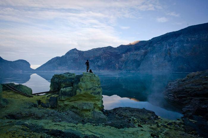Турист смотрит на озеро, расположившееся на дне кратера вулкана Иджен в Восточной Яве, 18 декабря 2013 года. Фото: Ulet Ifansasti / Getty Images
