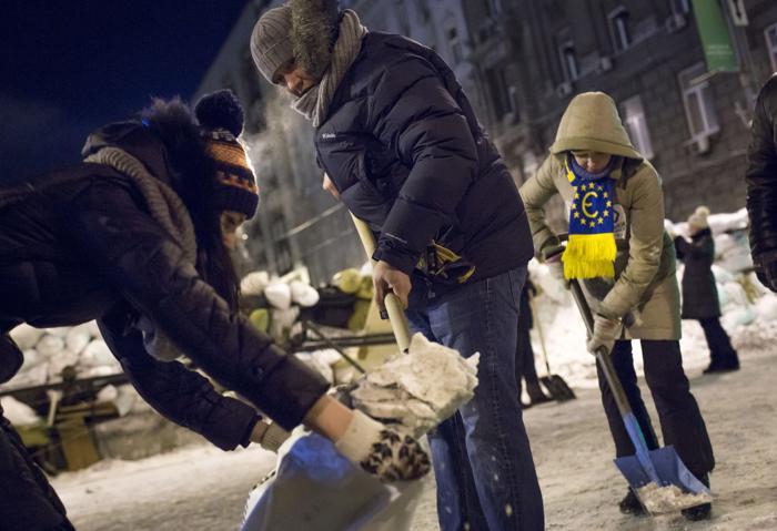 Протестующие на улицах, ведущих к Майдану, насыпают снег в мешки, чтобы строить новые баррикады 23 января 2014 года. Фото: Rob Stothard/Getty Images