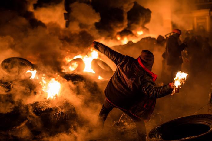 Протестующий бросает бутылку с зажигательной смесью во время столкновений с полицией на улице Грушевского в центре Киева 24 января 2014 года. Фото: Brendan Hoffman/Getty Images