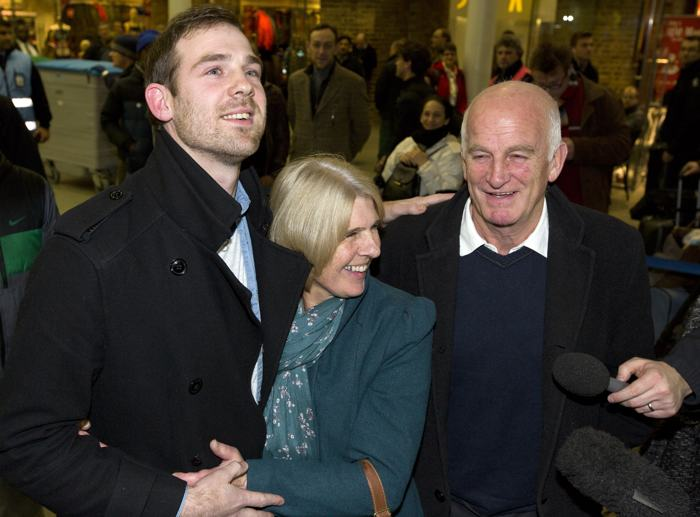 Журналист Кирон Брайан со своей матерью Энн и отцом Энди встретились на железнодорожном вокзале в Лондоне 27 декабря 2013 года, после того как вышли по амнистии из российской тюрьмы, где находились по делу о судне «Гринпис». Фото: JUSTIN TALLIS/AFP/Getty Images