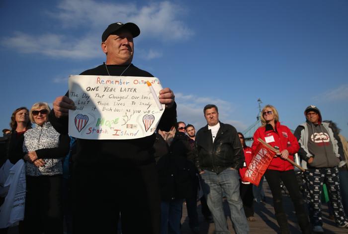 Жители района Статен-Айленд Нью-Йорка прошлись с почётным караулом по общественному пляжу 29 октября 2013 года в первую годовщину урагана «Сэнди», почтив память более 150 погибших. Фото:  John Moore / Getty Images