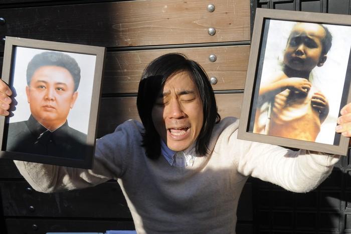 Протест  гражданки КНДР, держащей в руках портреты бывшего лидера страны Ким Чен Ира и её ребёнка, страдающего от голода, охватившего страну, Сеул, 3 декабря, 2010 год. Фото: PARK JI-HWAN/AFP/Getty Images