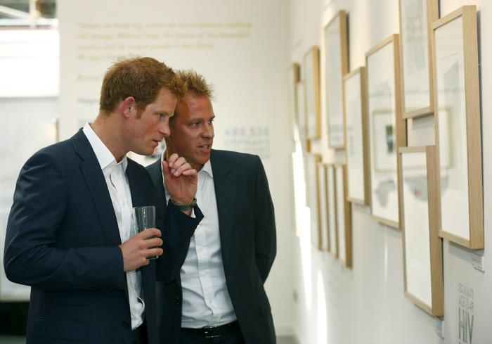 Принц Гарри (слева) и автор фотографий выставки Крис Джексон (справа) на закрытом показе благотворительной фотовыставки «Sentebale — истории надежды» в галерее Getty Images 25 июля 2013 года в Лондоне, Великобритания. Фото: Andrew Winning - WPA Pool/ Getty Images