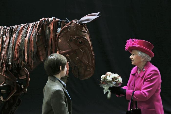 Королева Великобритании Елизавета II посмотрела «Боевого коня», исполненного актёрами, в день 50-летия Национального театра в Лондоне 22 октября 2013 года. Фото: Lefteris Pitarakis - WPA Pool/Getty Images