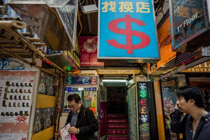 Мужчина (слева) у пункта обмена валюты в Гонконге 22 ноября 2012 года. Фото: Philippe Lopez/AFP/Getty Images