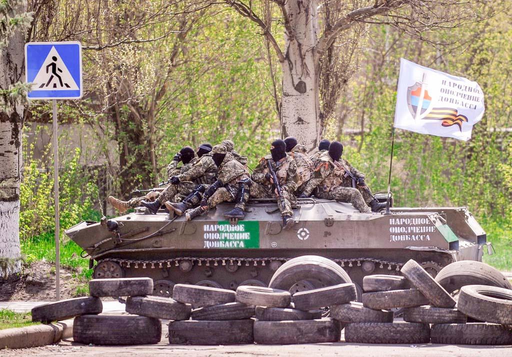 Вооружённые люди в военной форме на бронетранспортёре под флагом «Народное ополчение Донецка», 18 апреля, 2014 год. Фото: GENYA SAVILOV/AFP/Getty Images