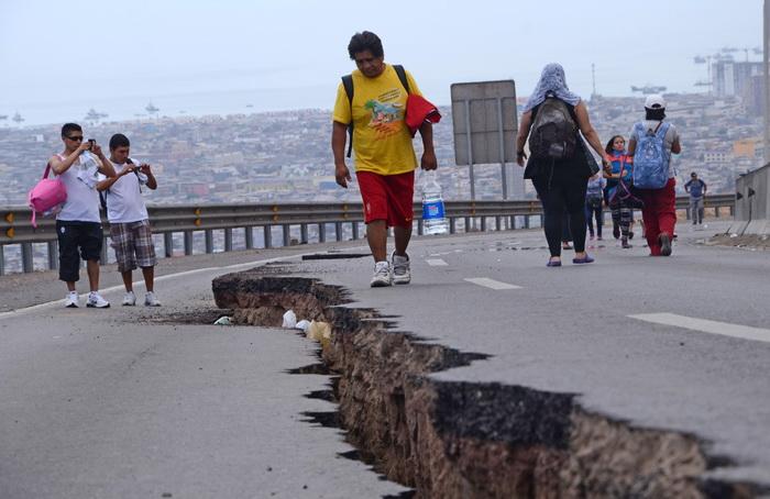 Люди гуляют около трещины, образовавшейся в ходе мощного землетрясения в городе Икике (Чили) 2 апреля 2014 года. Фото: Aldo Solimano/AFP/Getty Images