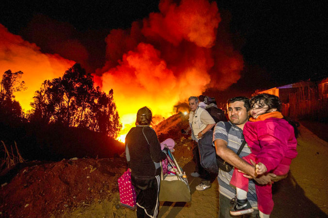 Местные жители уходят от места пожара в Вальпараисо (Чили) 13 апреля 2014 года. Более 10 тысяч людей эвакуировано и 15 погибли от стихии. Фото: MARTIN BERNETTI/AFP/Getty Images