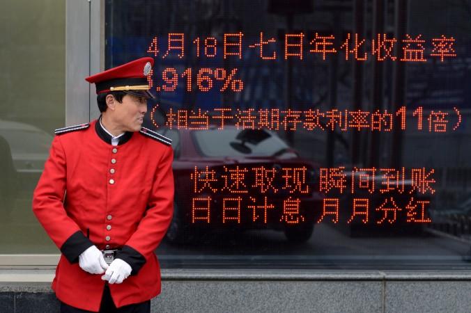 Охранник стоит перед электронным табло у входа в банк в Пекине 23 апреля 2013 года. Фото: WANG ZHAO/AFP/Getty Images