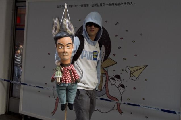 Житель Гонконга держит 1 января 2014 году куклу-марионетку, изображающую главу администрации Лян Чжэнь-ина с волчьими ушами. Фото: AFP/Getty Images