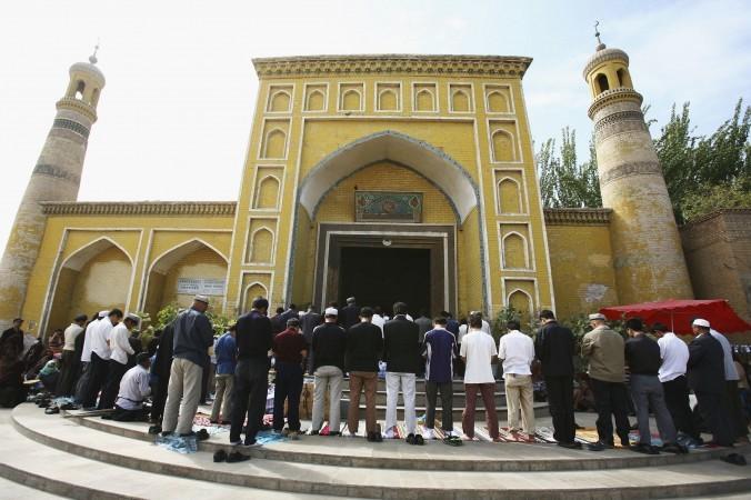 Мусульмане молятся возле мечети 22 сентября 2006 года в г. Каши Синьцзян-Уйгурского автономного района на северо-западе Китая. Губернатор традиционно мусульманской провинции Синьцзян недавно заявил, что исламисты хотят запретить смех на свадьбах и слёзы на похоронах. Он также обвинил их в террористической деятельности. Фото: China Photos/Getty Images