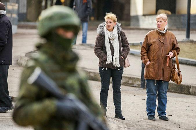 Женщины наблюдают за скоплением военных в Симферополе 1 марта 2014 года, когда российские солдаты заняли аэропорт города. Фото: Sean Gallup/Getty Images