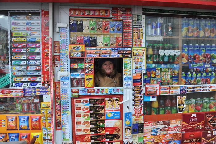 Продавщица выглядывает из своего магазина в центре Киева. Фото: YURIY DYACHYSHYN/AFP/Getty Images