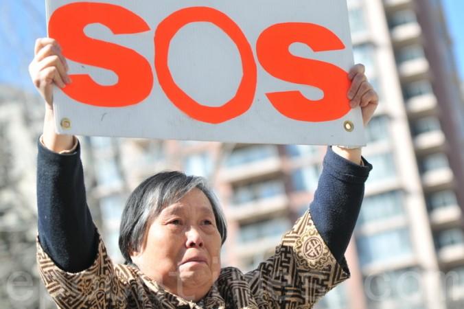 Хуан Цзиньлин держит плакат на пресс-конференции в Калгари 15 апреля, призывая помочь спасти свою дочь Чэнь Инхуа. Фото: Wu Weilin/Epoch Times