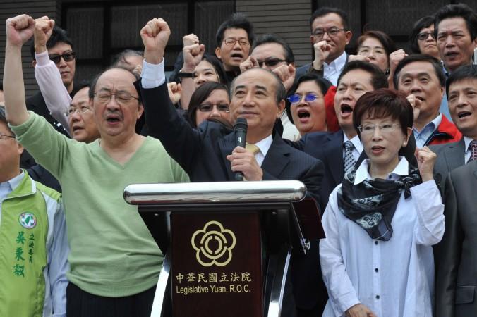 Спикер тайваньского парламента Ван Цзинь-пин (в центре) и депутаты от Гоминьдана выкрикивают лозунги перед зданием парламента в Тайбэе 6 апреля 2014 года. Спикер заявил, что приостановит принятие торгового соглашения с Китаем. Фото: Mandy Cheng/AFP/Getty Images