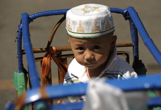 Уйгуры в Китае могут носить традиционные головные уборы только по праздникам. Фото: PETER PARKS/AFP/Getty Images