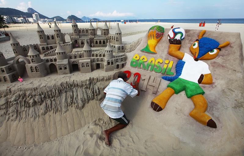 Художник на пляже создаёт из песка символы Чемпионата мира по футболу 2014 в Бразилии, в Рио-де-Жанейро. Местные жители готовятся к 20 чемпионату, который стартует 12 июня. 32 команды со всего мира проведут 64 игры в 12 бразильских городах. Фото: Mario Tama/Getty Images