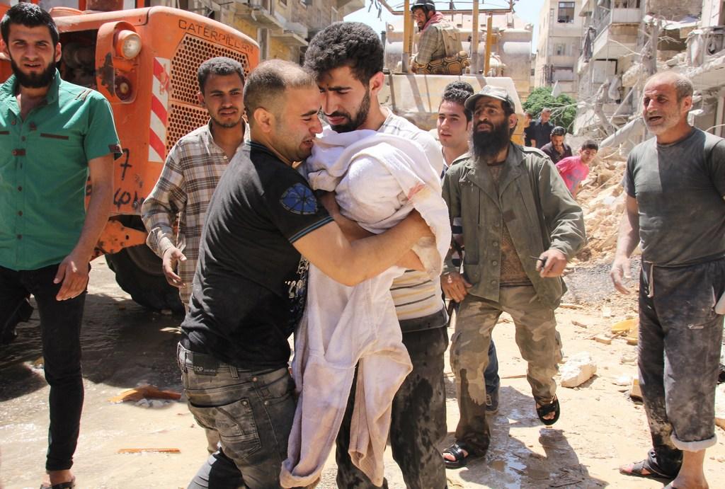 Отец трёхмесячного ребёнка получает от спасателя его тело, извлеченное из под завалов, после авиабомбёжки правительственных войск Сирии, Алеппо, 26 мая, 2014 год. Фото: BARAA AL-HALABI/AFP/Getty Images