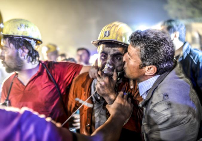 Мужчина целует  сына,  спасённого после взрыва  из шахты в Манисе, Турция, 14 мая, 2014 год, Фото:  BULENT KILIC/AFP/Getty Images