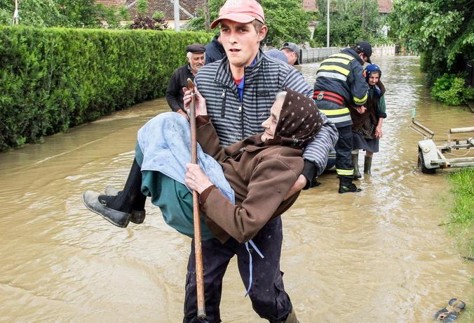 Сербский спасатель несет пожилую женщину из ее затопленного дома в селе Обрез, 17 мая, 2014 год. Фото: SASA DJORDJEVIC/AFP/Getty Images