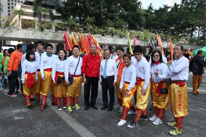 Депутат от DAB («Демократический альянс за улучшение и прогресс Гонконга») и организатор танцев льва Чхань Кхам-лам (в центре, с синим галстуком) вместе с участниками танцевальной группы. Крайний справа участник был ранее замечен в зелёной униформе «Ассоциации содействия молодёжи Гонконга», которая осуществляет нападки на последователей Фалуньгун. Фото: theepochtimes.com