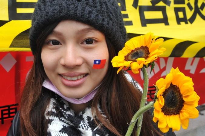 Девушка держит подсолнухи и носит на лице наклейку национального флага Тайваня в знак поддержки протестующих студентов, занявших здание парламента в Тайбэе 21 марта 2014 года. Фото: Mandy Cheng/AFP/Getty Images