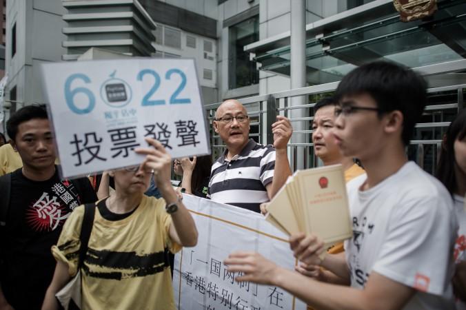 Участник демонстрации призывает граждан проголосовать 22 июня на референдуме по введению всеобщего избирательного права, Гонконг, 11 июня 2014 года. Веб-сайт, связанный с референдумом, недавно был взломан. Фото:PhilippeLopez/AFP/GettyImages