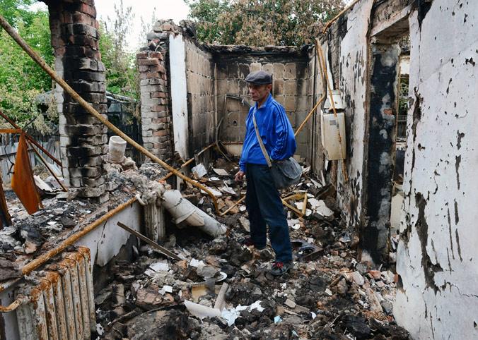 Мужчина на развалинах своего дома, разрушенного в результате артиллерийского обстрела, в осаждённом Славянске 24 июня 2014 года. Фото: JOHN MACDOUGALL/AFP/Getty Images