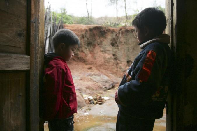 Двое пострадавших от отравления свинцом детей в своём доме в уезде Часянь провинции Хунань 16 марта 2007 года. Фото: China Photos/Getty Images