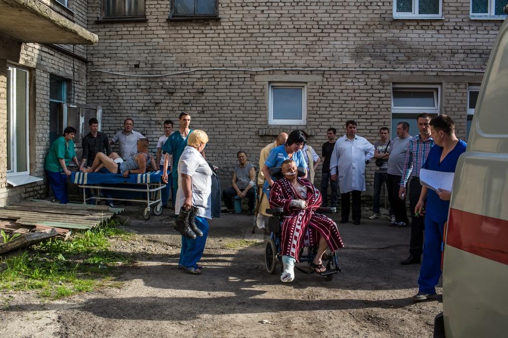 Украинские солдаты, раненые в начале боя под Волновахой, передаются  скорой помощи, Украина, Волноваха, 22 мая, 2014 год. Фото: Brendan Hoffman/Getty Images