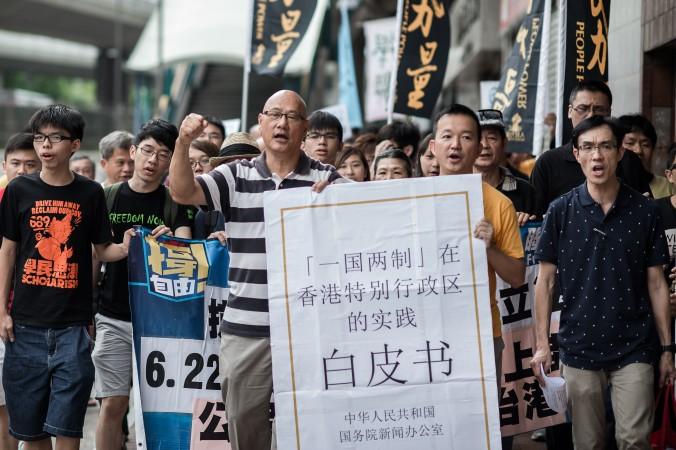 Демонстранты в Гонконге выкрикивают лозунги, держа в руках макет «белой бумаги» Пекина. Китай выпустил документ, свидетельствующий об ужесточении контроля над Гонконгом. Фото: Philippe Lopez/AFP/Getty Images