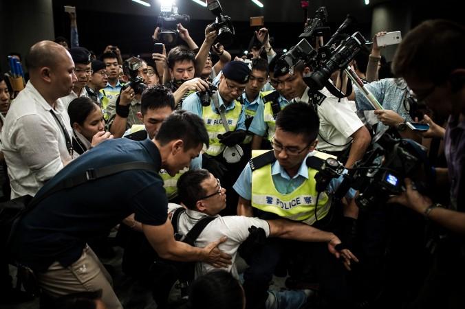 Спецназ разгоняет демонстрантов, протестующих возле Законодательного совета в Гонконге 14 июня 2014 года. Участники протеста выступили против плана правительства превратить сельскохозяйственные угодья в микрорайоны. Фото: Philippe Lopez/AFP/Getty Images