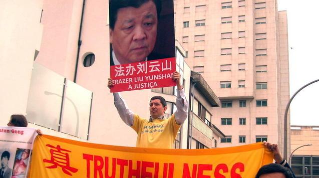 Последователь Фалуньгун в Португалии держит портрет министра пропаганды Китая с подписью «Судить Лю Юньшаня». Фото: Великая Эпоха