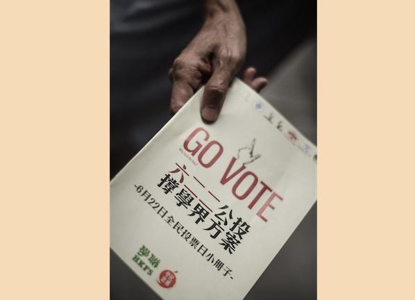 Активист раздаёт листовки с просьбой принять участие в референдуме 22 июня по вопросу введения всеобщего избирательного права, Гонконг, 12 июня 2014 года. «Белая книга», выданная Гонконгу китайским режимом, похоже, вызвала интерес людей к референдуму и одновременно оттолкнула народ Тайваня от Китая. Фото: Philippe Lopez/AFP/Getty Images