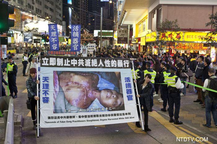 Шествие последователей Фалуньгун в Гонконге. На плакате погибший в китайской тюрьме сторонник Фалуньгун, у которого вырезали органы для продажи. Фото: NTD TV